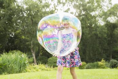 Father and daughter playing with large bubbles in backyard