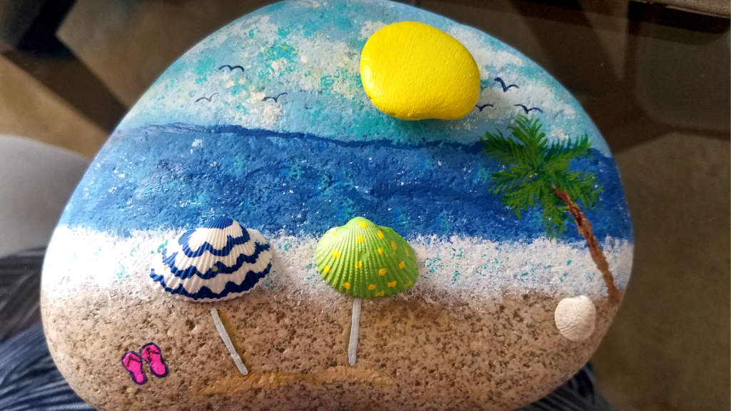 beach scene painted rock with shells